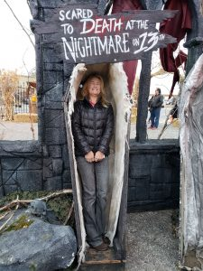Woman posing for photo in scared to death coffin in courtyard of Nightmare on 13th